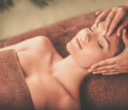 Young woman having face massage in a spa salon.  Stock Photos