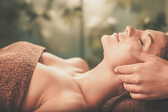 Young woman having face massage in a spa salon Stock Photo