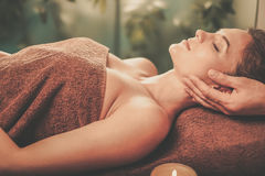 Young woman having face massage in a spa salon Stock Photography