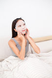 Young woman having facial mask treatment. And sitting on bed stock images