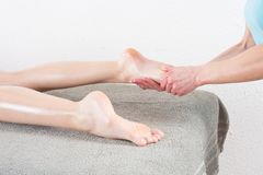 Woman having feet massage in beauty salon stock image
