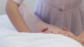Young woman having feet massage in beauty spa salon, close up. Masseur kneads the foot and leg of a young beautiful girl