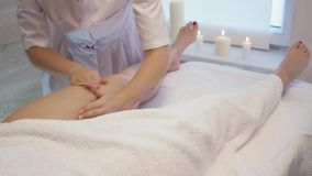 Young woman having feet massage in beauty spa salon. Masseur kneads the foot and leg of a young beautiful girl at candle