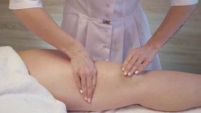 Young woman having feet massage in beauty spa salon. Masseur kneads the foot and leg of a young beautiful girl. Close Up