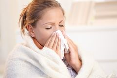 Young woman having flu blowing her nose. Young woman having flu, feeling bad, blowing her nose, wrapped up in blanket Royalty Free Stock Photo