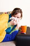 Young woman having flu, blowing her nose Stock Photography