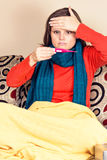 Young woman having flu and  checking a thermometer Stock Images