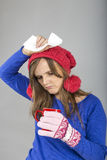 Young woman having flu with gloves  and knitted scarf holding a Royalty Free Stock Photography