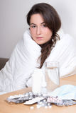 Young woman having flu with pills on the table Royalty Free Stock Photo