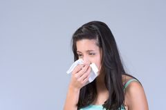 Young woman having Flu and sneezing. Girl covers her mouth and nose with handkerchief Royalty Free Stock Photo