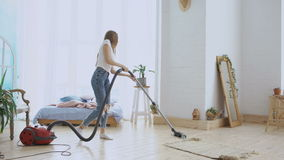 Young woman having fun cleaning house with vacuum cleaner dancing and singing at home stock footage