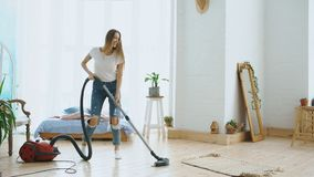 Young woman having fun cleaning house with vacuum cleaner dancing and singing at home royalty free stock photography