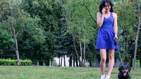 Young woman having fun with dachshund dog in park talking on the phone. stock footage