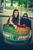 Young woman having fun in electric bumper car Stock Photos