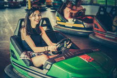 Young woman having fun in electric bumper car Royalty Free Stock Photo