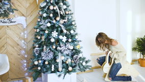Young woman having fun and joy near christmas tree on party stock footage