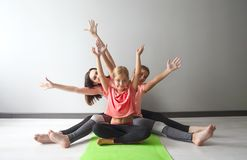 Young woman having fun with kids doing yoga. Young women having fun with kids doing yoga. Family sport concept stock photography