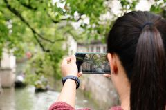 Young woman having fun in local canal city in China with camera on smartphone making pictures stock image