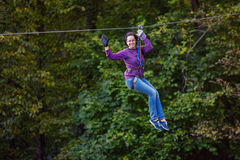 Young woman having fun on long rope route Stock Photos