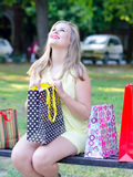 Young woman having fun in the park after shopping Royalty Free Stock Image