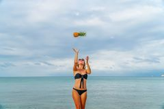 Young Woman Having Fun with Pineapples on Beach Stock Photo