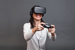 Young woman and having fun playing a virtual reality video game Stock Image