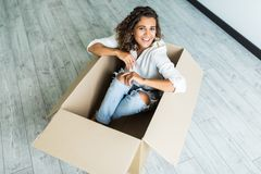 Young woman having fun and riding in cardboard boxes at new home royalty free stock photo