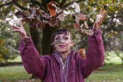 Young woman having fun throwing up the leaves. In the park. Concept of people in autumn stock image