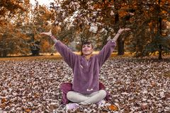 Young woman having fun throwing up the leaves. In the park. Concept of people in autumn stock photography