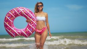 Young woman having fun with toy Inflatable ring donut on the beach. Young woman having fun with toy Inflatable ring donut on the beach stock video footage