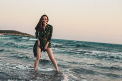 Young woman having fun in the water on the beach at red sunset, smile, relax, entertainment.  royalty free stock photo
