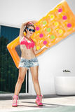Young woman having fun with yellow mattress Stock Photo