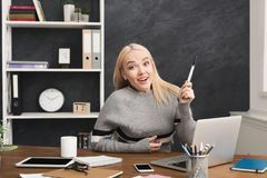 Young woman having great idea at office. Young happy woman having great idea, sitting at office, copy space. Found something interesting, raising hand upwards Royalty Free Stock Photo
