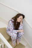 Young woman having headache while sitting on stairway Royalty Free Stock Image