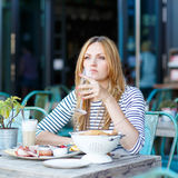 Young woman having healthy breakfast in outdoor cafe Royalty Free Stock Images