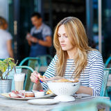 Young woman having healthy breakfast in outdoor cafe Stock Photos