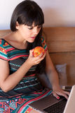 Young woman having a healthy snack while working Royalty Free Stock Image