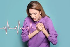 Young woman having heart attack. On color background stock image
