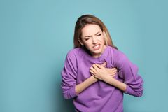 Young woman having heart attack. On color background royalty free stock photos
