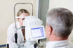 Young woman having her eyes examined by an eye Royalty Free Stock Photos