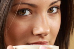 Young woman is having her tea/coffee. Young woman with beautiful face is having her tea/coffee Royalty Free Stock Photography