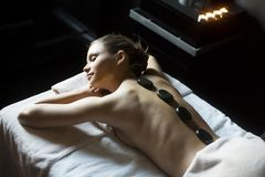 Young woman having a hot stone massage therapy Stock Photo