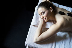 Young woman having a hot stone massage Royalty Free Stock Photo