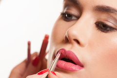 Young woman having lip gloss applied Stock Images