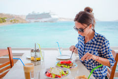 Young woman having lunch with delicious fresh greek salad, frappe and brusketa served for lunch at outdoor restaurant Stock Image