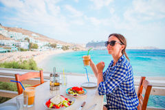 Young woman having lunch with delicious fresh greek salad, frappe and brusketa served for lunch at outdoor restaurant Stock Photo