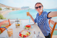 Young woman having lunch with delicious fresh greek salad, frappe and brusketa served for lunch at outdoor restaurant. Delicious fresh greek salad and musaka Stock Photography