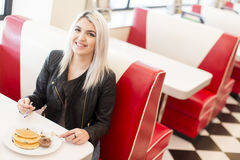 Young woman having lunch in a diner. Young woman having a lunch in a diner Stock Photography
