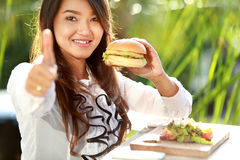 Young woman having lunch and give thumbs up for delicious food Royalty Free Stock Photography