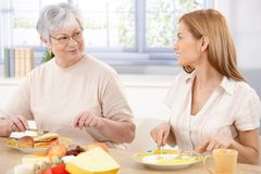 Young woman having lunch with mother smiling. Young woman having lunch with her mother, talking, smiling royalty free stock images
